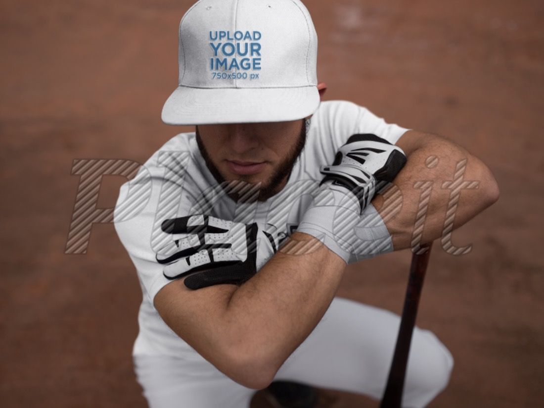 batter squatting while wearing a baseball cap