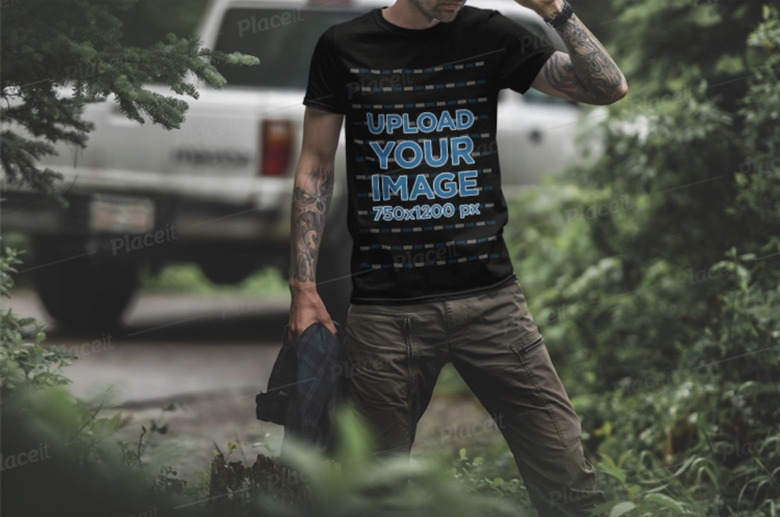 black t-shirt mockup of a tattooed man in the woods