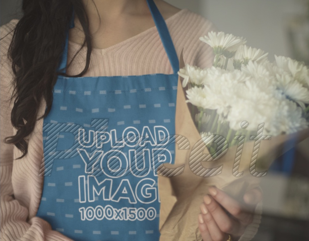 closeup of an apron mockup being worn by a girl holding a bouquet of flowers
