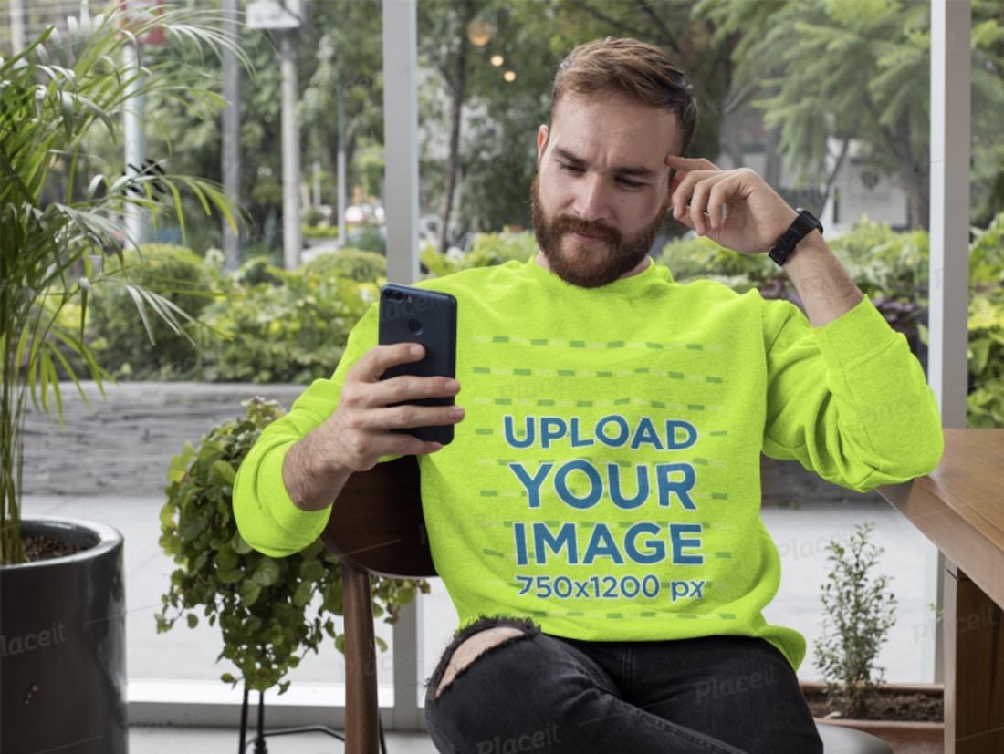 crewneck sweatshirt mockup of a man checking his phone