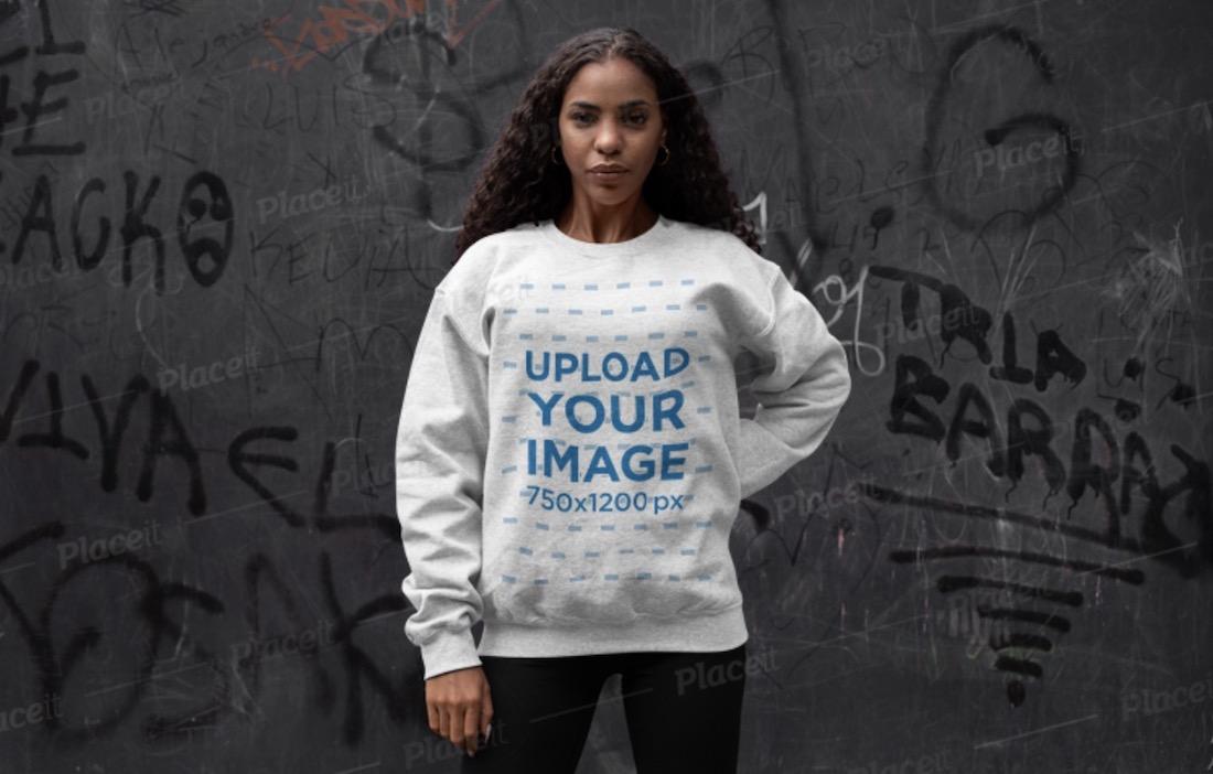 crewneck sweatshirt mockup of a woman posing in front of a graffiti wall