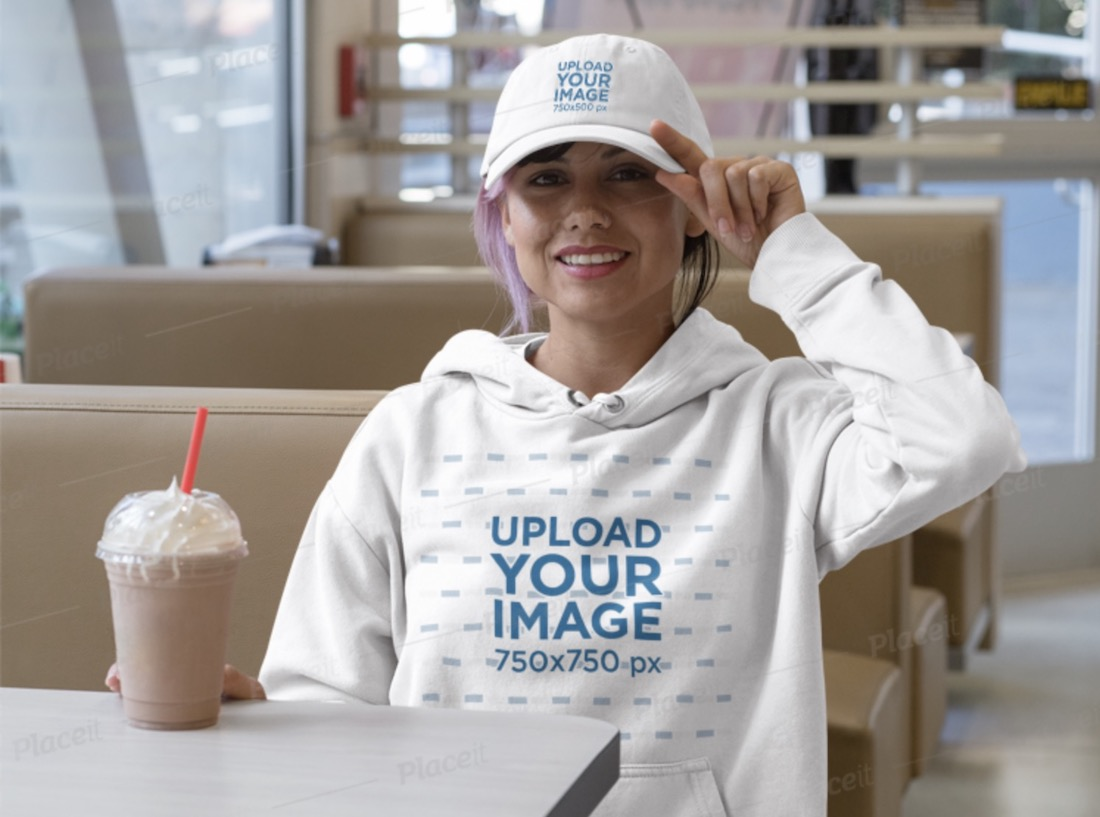 hoodie mockup featuring a woman at a restaurant wearing a baseball cap