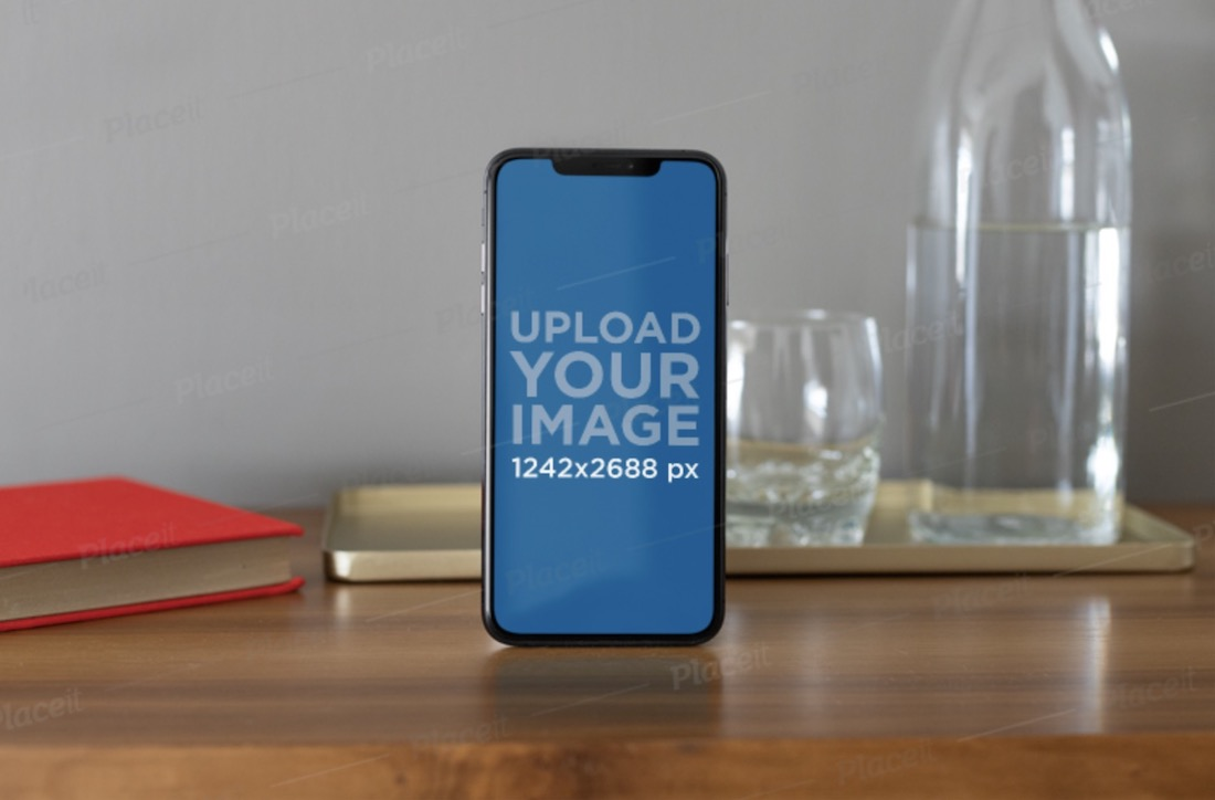 iphone xs max mockup standing next to some glass recipients