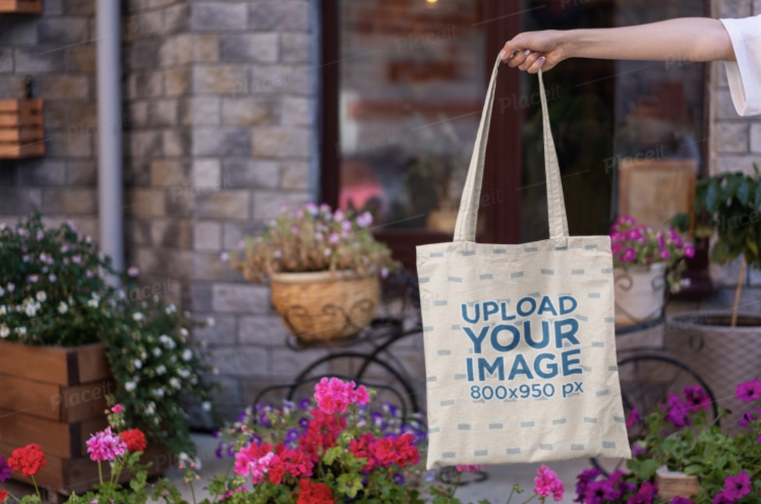 mockup featuring a woman s hand holding a tote bag by some flower pots