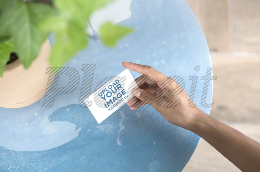 mockup of a business card being held next to a plant pot