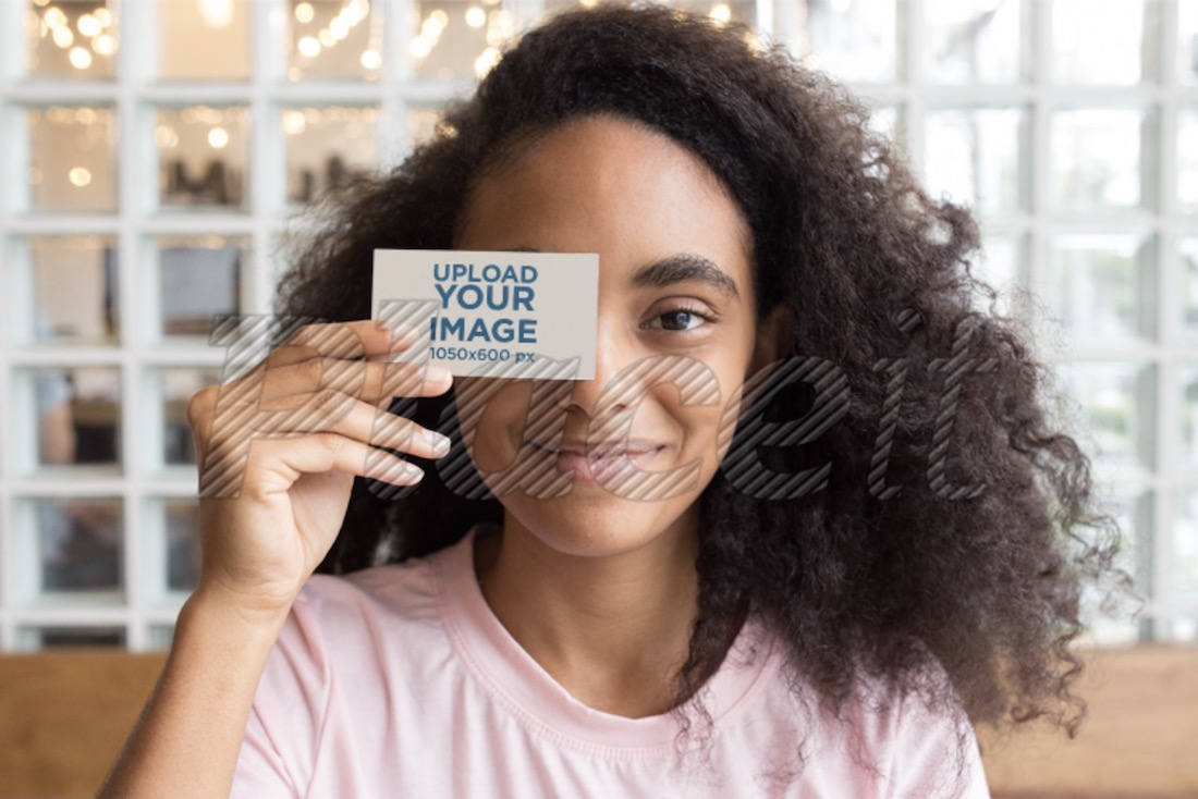 mockup of a girl holding a business card against her face