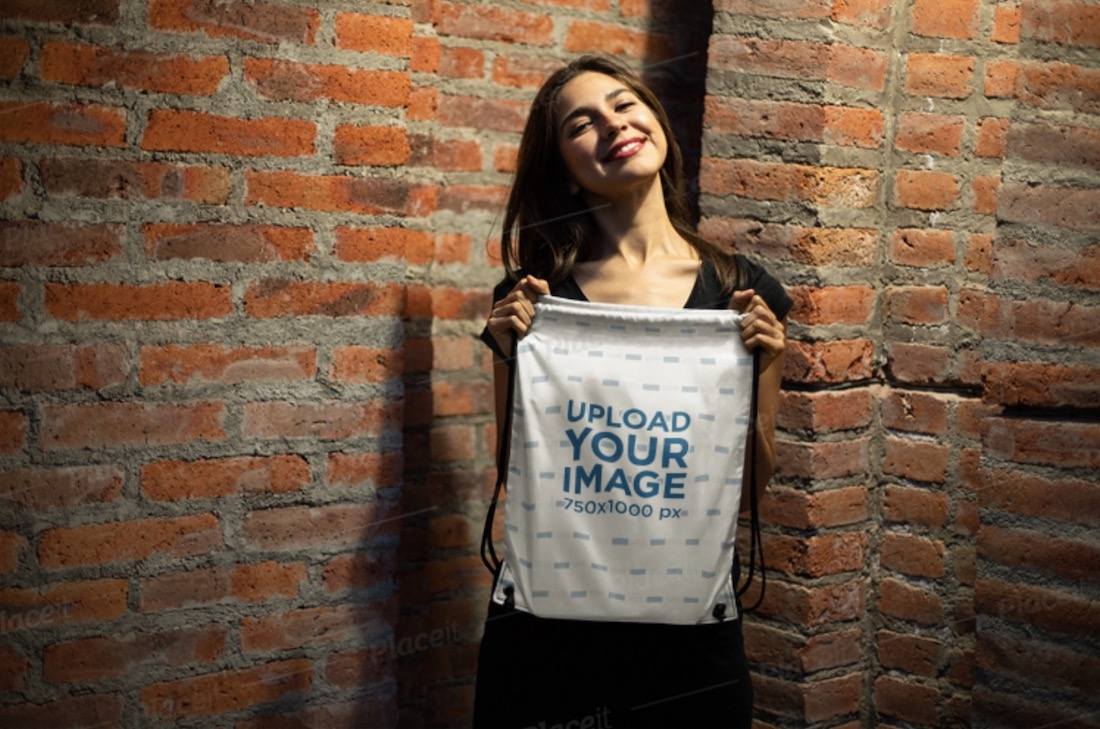 mockup of a happy young woman showing off her drawstring bag