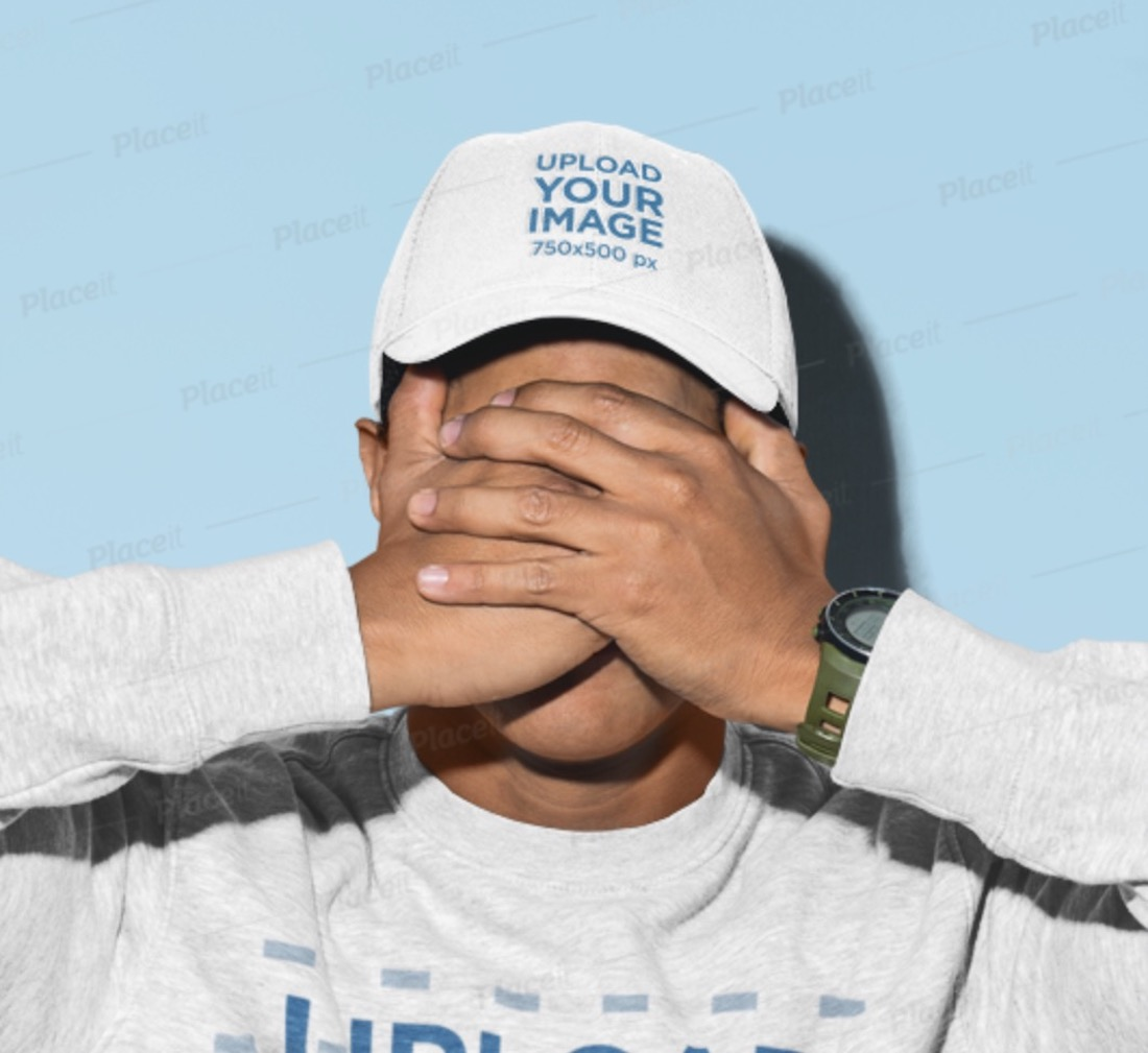 mockup of a man covering his face wearing a baseball cap