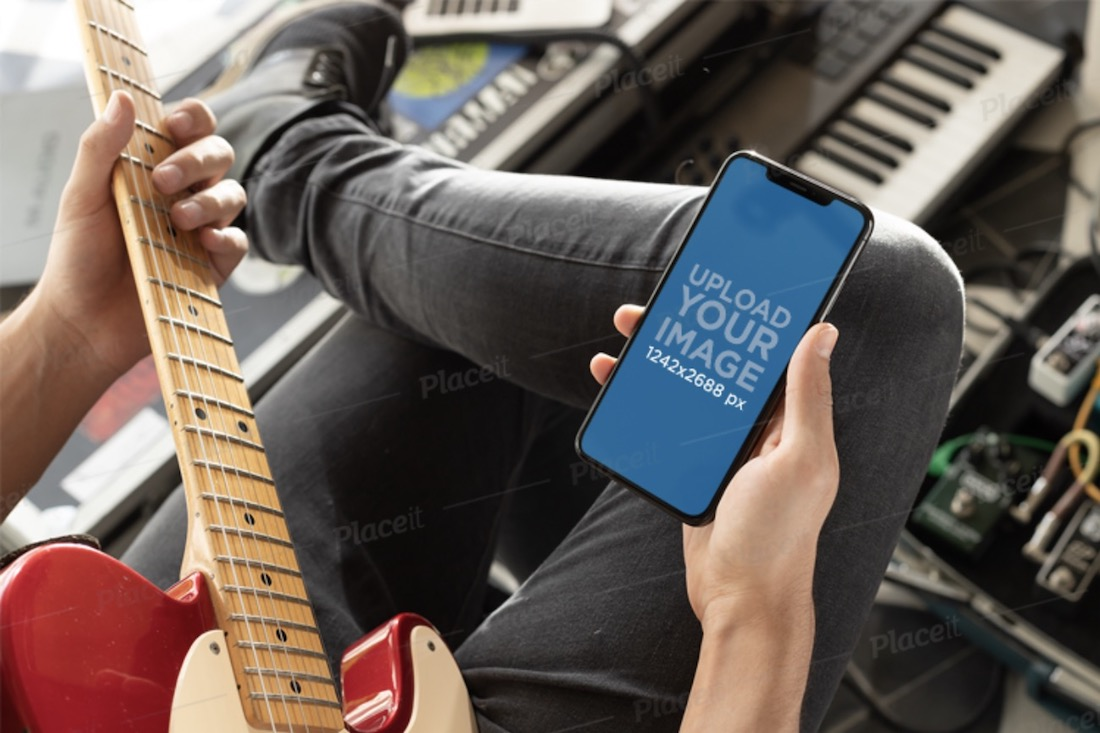 mockup of a man watching his iphone xs max while playing guitar