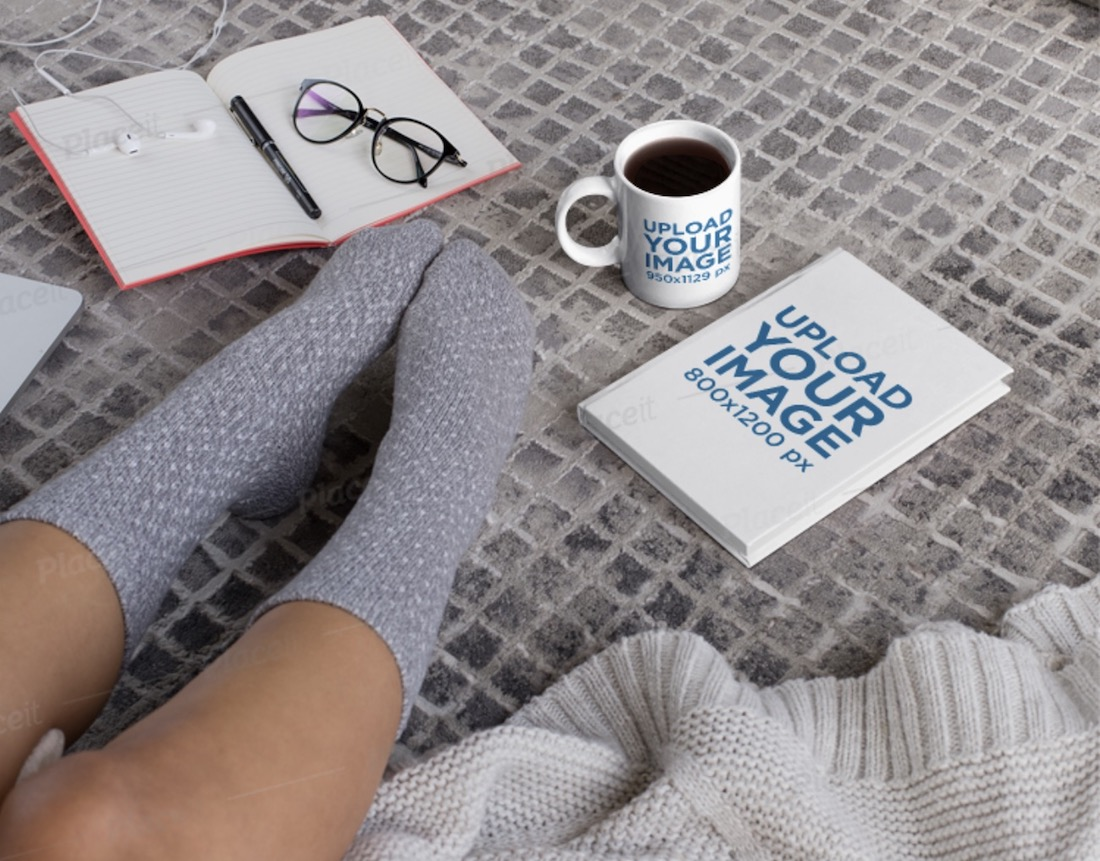 mockup of an 11 oz mug and a book on the floor
