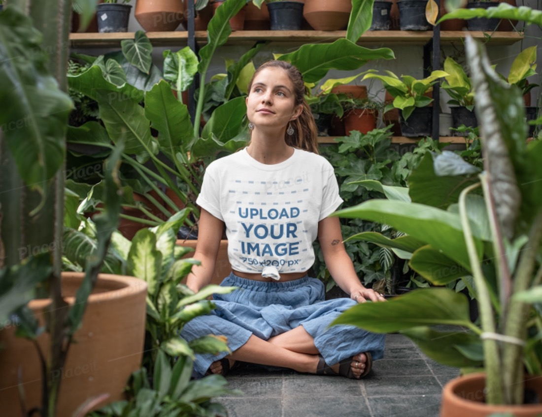 t-shirt mockup of a woman sitting in a greenhouse