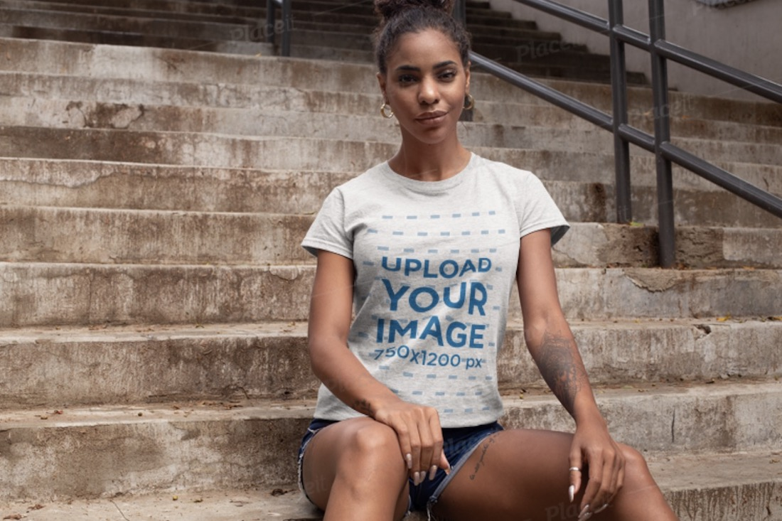 t-shirt mockup of a woman sitting on concrete stairs
