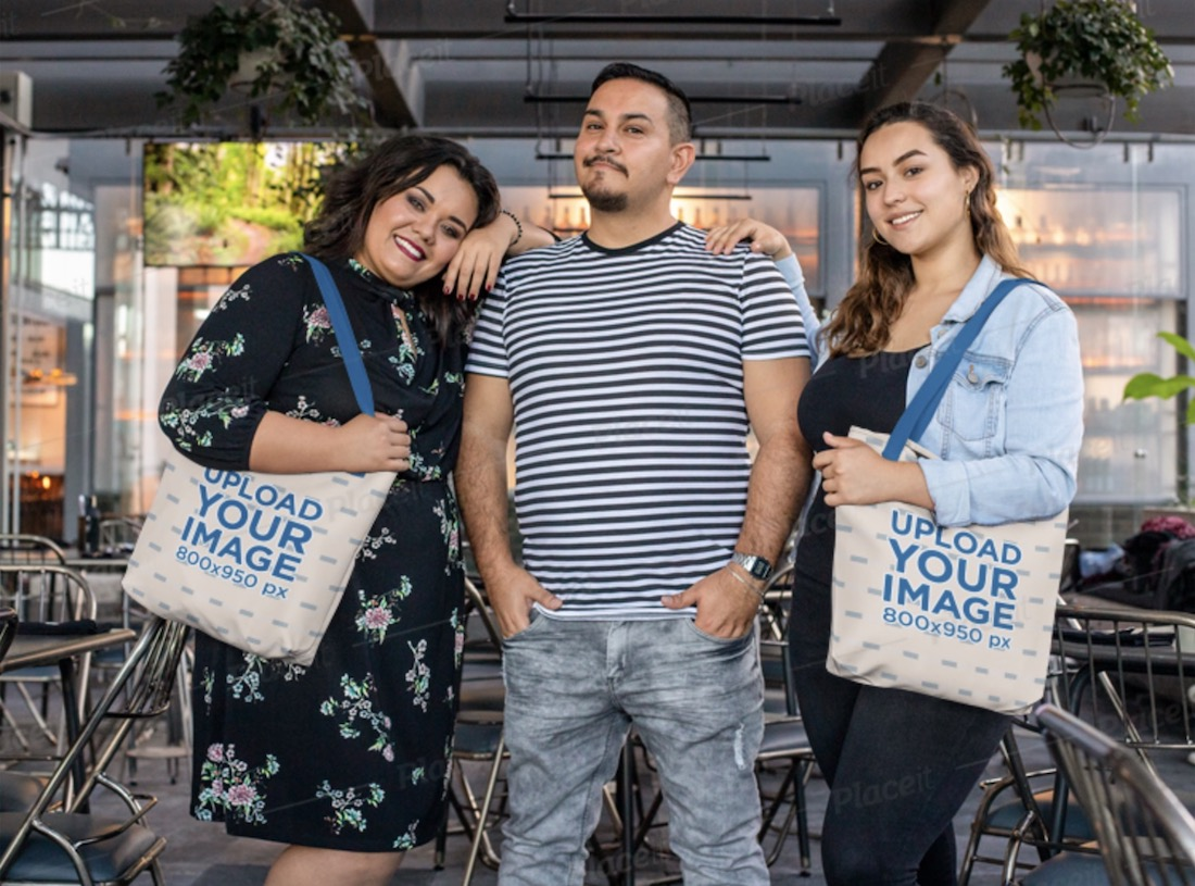 tote bag mockup featuring two women posing with their friend