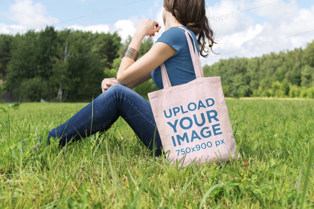 tote bag mockup of a woman sitting at a green meadow