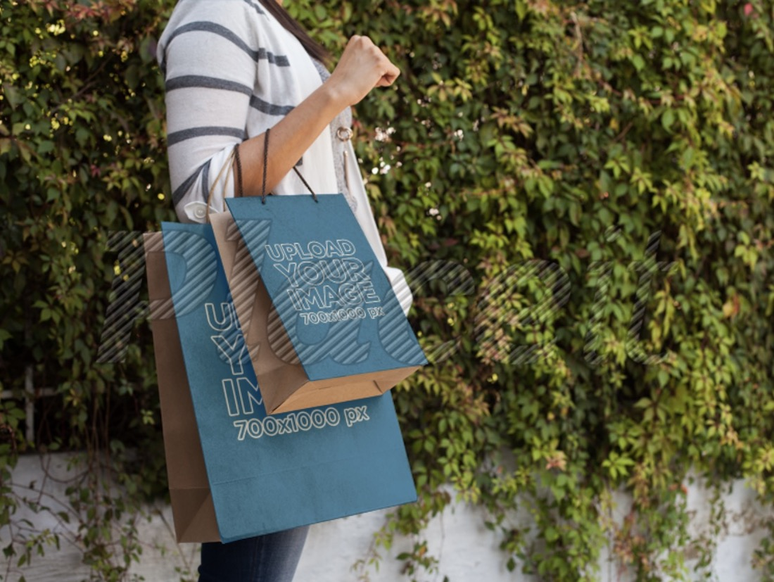 woman carrying two paper shopping bags