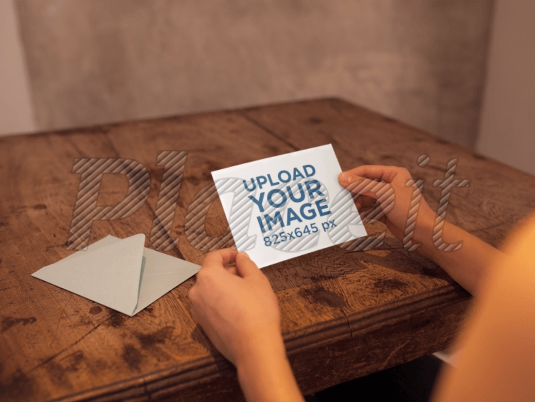 woman holding a greeting card mockup on a wooden table